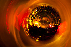 """Beauty at the Bottom: Red Wine 4"" - This is a photograph of a red wine bottle bottle, shot right down inside the mouth of the bottle. A fire behind the bottle provides the main lights source."