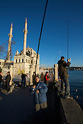 Istanbul. Ortako?y. Fishermen in front of Ortako?y Mosque and Bosporus Bridge.