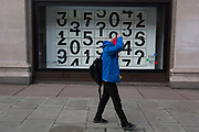 A shopper walks past a window display that features numbers - part of a design theme called 'State of the Arts', at the Selfridges department store on Oxford Street, on 4th March 2019, in London England. Darren Almond's piece 'Chance Encounter 004', consists of a grid formed from rectangular panels, featuring fragmented numbers that appear to scroll across the surface. <br /> State of the Arts is a gallery of works by nine crtically-acclaimed artists in Selfridges windows to celebrate the power of public art. Each of the artists are involved in creating a site-specific artwork at one of the new Elizabeth line stations as part of the Crossrail Art Programme.