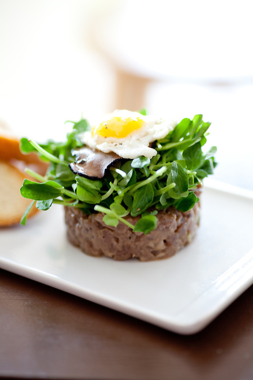 Lamb Tartare with Black Truffle and Pea Shoots Topped with a Quail Egg at Home WIne Kitchen in St. Louis, MO.