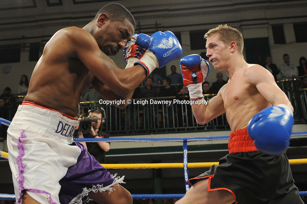 Charlie Hoy (red trim shorts) defeats Delroy Spencer in a 4x3 min Flyweight contest at York Hall, Bethnal Green, London on Friday 13th January 2012. Queensbury Promotions © Leigh Dawney 2012
