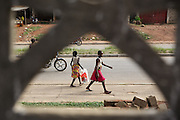 Girls walk down the main street in Katiola, Cote d'Ivoire on Saturday July 13, 2013.