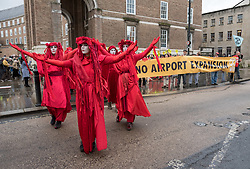 "© Licensed to London News Pictures. 31/01/2020. Bristol, UK. Extinction Rebellion's Red Rebel Brigade at the ""No Bristol Airport Expansion"" march and rally in the city centre, organised by Bristol Airport Action Network (BAAN) and Extinction Rebellion Bristol. Bristol Airport, which is situated in North Somerset, has plans to increase capacity for 12 million passengers a year, up from its current capacity of 10 million by 2026, and their application is due to be considered at a special meeting of North Somerset's Planning and Regulatory Committee on February 10 at 6pm. North Somerset Council officers have recommended the application be approved despite more than 5,400 objections and around 2,200 letters of support. Objections have highlighted the detrimental effects for the local communities including increased air and noise pollution, increased traffic congestion and the loss of Greenbelt land around the airport, but the urgent need to tackle climate change is one of the main reasons why people are objecting. Photo credit: Simon Chapman/LNP."