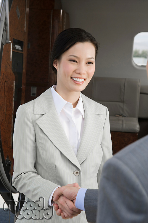 Mid-adult Asian businesswoman shaking hands with mid-adult businessman inside airplane.