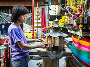 30 DECEMBER 2015 - BANGKOK, THAILAND:  A woman prays at a small shrine in Bang Chak Market. The market is supposed to close permanently on Dec 31, 2015. The Bang Chak Market serves the community around Sois 91-97 on Sukhumvit Road in the Bangkok suburbs. About half of the market has been torn down. Bangkok city authorities put up notices in late November that the market would be closed by January 1, 2016 and redevelopment would start shortly after that. Market vendors said condominiums are being built on the land.           PHOTO BY JACK KURTZ