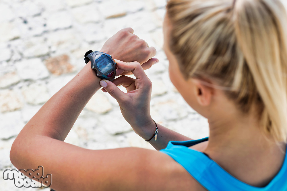 High angle view of young attractive woman looking at her wristwartch after running in park
