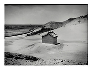 Sand, like fresh snow, accumulates on top of and around a village Buddhist temple.  Ironically, Yellow River irrigation fed wet rice paddy fields can be seen in the background, near Shikong, Ningxia, China.