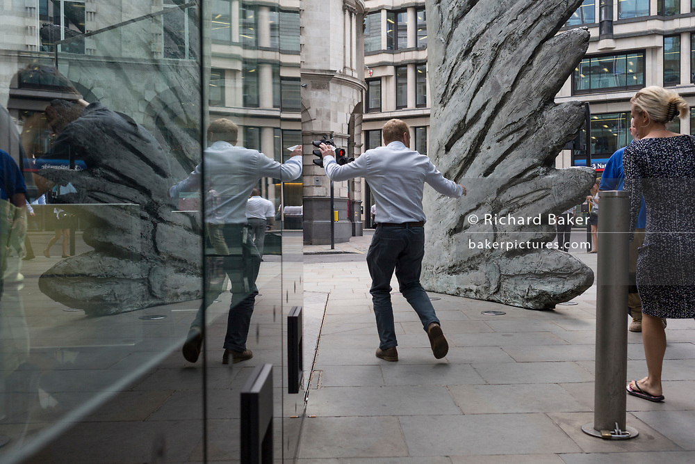 Londoners walk past the sculpture entitled City Wing on Threadneedle Street in the City of London, the capital's financial district, on 25th July 2018, in London, England. City Wing is by the artist Christopher Le Brun. The ten-metre-tall bronze sculpture is by President of the Royal Academy of Arts, Christopher Le Brun, commissioned by Hammerson in 2009. It is called 'The City Wing' and has been cast by Morris Singer Art Founders, reputedly the oldest fine art foundry in the world.
