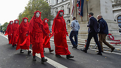 © Licensed to London News Pictures. 09/10/2019. LONDON, UK.  Members of the Red Brigade, supporters of Extinction Rebellion's demonstration, walk silently down Whitehall passing The Cenotaph during day 3 of Extinction Rebellion's climate change protest in the capital.  Some of the activists had used glued themselves to the road.  Photo credit: Stephen Chung/LNP