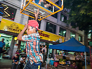 29 OCTOBER 2015 - YANGON, MYANMAR: A worker jumps off a spinning Ferris Wheel during a street carnival in central Yangon. Electricity is scarce in Myanmar, especially in rural areas, and most traveling carnivals use human powered rides. Workers climb to the top of the Ferris Wheel and then pull it around getting it spinning. They do the same with Merry Go Rounds, but instead of climbing to the top they pull it around. The carnival coincided with the Thadingyut Festival, the Lighting Festival of Myanmar, which is held on the full moon day of the Burmese Lunar month of Thadingyut, October or November on the Gregorian calendar. The carnival featured food, rides and games.      PHOTO BY JACK KURTZ