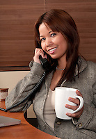 Young woman talking in the phone a having a cup of coffee in the office.