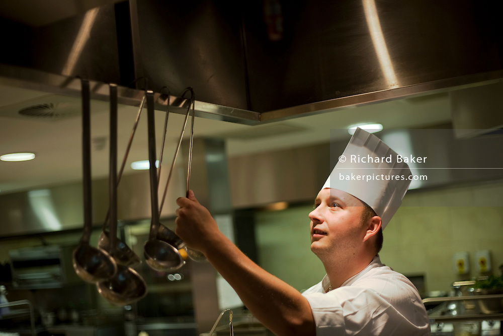 "Showing the face of a man who enjoys his job, a chef reaches for a ladle hanging inside an extractor cover in the kitchens at the Vivre restaurant in Sofitel, a 605 bedroom, 27 suite and 45 meeting room accommodation and business hub Heathrow Airport's hub hotel attached to Terminal 5. The man is wearing a tall chef's hat called a toque and his uniform is pristine to reflect the hygiene standards expected of this luxury hotel and restaurant. From writer Alain de Botton's book project ""A Week at the Airport: A Heathrow Diary"" (2009). ."