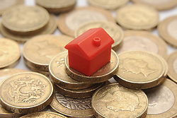 File photo dated 27/01/15 of a plastic model of a house on a pile of one pound coins. The trade association UK Finance has said that mortgage lending to home buyers has reached its highest levels for February in over a decade.