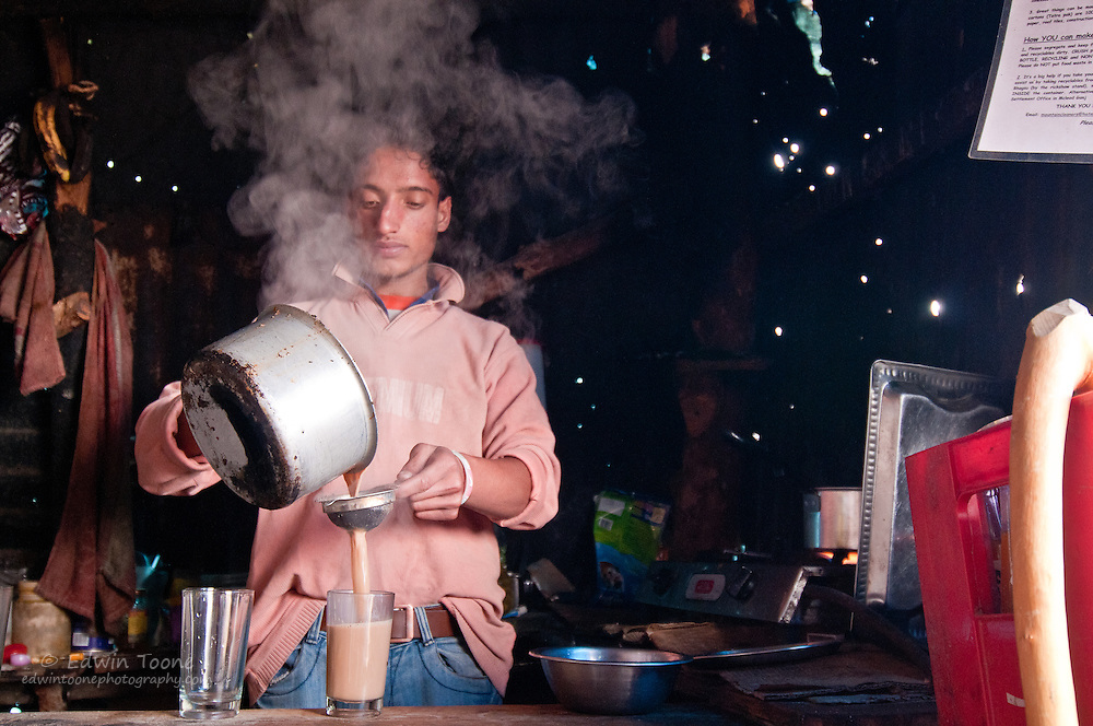 Steam rises up in from of the clerks face as he pours hot tea in Dharamsala, India.