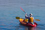 A father and daughter kayaking in an inlet near the ocean.