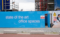 Hoarding around construction site for offices at the docklands in Dublin Ireland