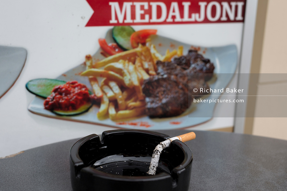 Detail of a burned-out cigarette and steak medallions and chips in the Slovenian capital, Ljubljana, on 28th June 2018, in Ljubljana, Slovenia.