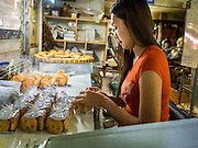 "06 FEBRUARY 2015 - BANGKOK, THAILAND: A worker at Thanusingha Bakery packages freshly baked traditional Thai Catholic desert cakes. The cakes are called ""Kanom Farang Kudeejeen"" or ""Chinese Monk Candy."" The tradition of baking the cakes, about the size of a cupcake or muffin, started in Siam (now Thailand) in the 17th century AD when Portuguese Catholic priests accompanied Portuguese soldiers who assisted the Siamese in their wars with Burma. Several hundred Siamese (Thai) Buddhists converted to Catholicism and started baking the cakes. When the Siamese Empire in Ayutthaya was sacked by the Burmese the Portuguese and Thai Catholics fled to Thonburi, in what is now Bangkok. The Portuguese established a Catholic church near the new Siamese capital. Now just three families bake the cakes, using a recipe that is 400 years old and contains eggs, wheat flour, sugar, water and raisins. The same family has been baking the cakes at the Thanusingha Bakery, near Santa Cruz Church, for more than five generations. There are still a large number of Thai Catholics living in the neighborhood around the church.        PHOTO BY JACK KURTZ"