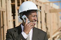 Surveyor using mobile phone on construction site