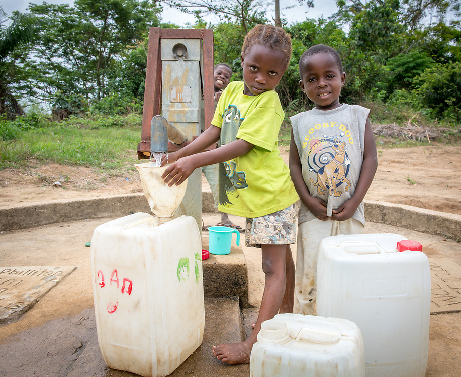 A young girl pumps water and a boy stands next to her, both pose for the camera in Ganta, Liberia