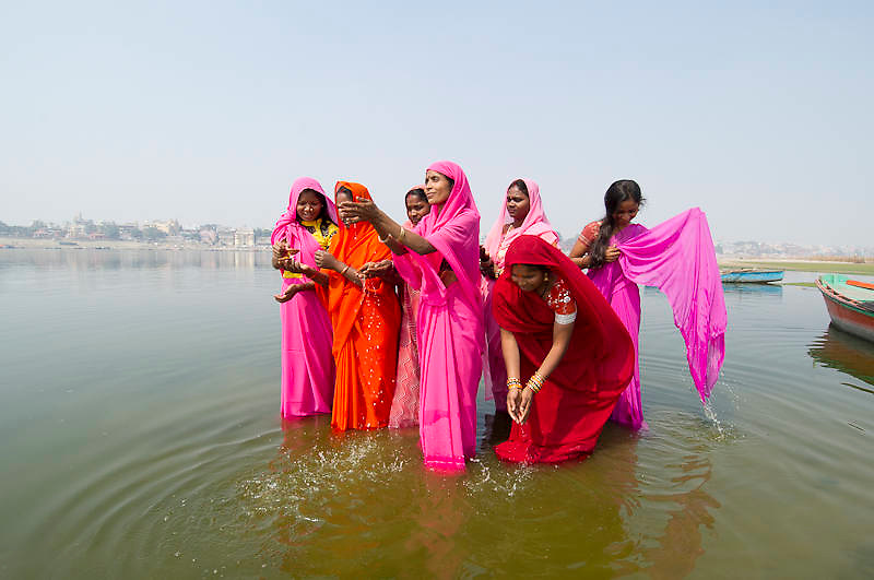 Indian women performing their morning prayer standing in the holy water of river Ganges (Ganga) in Varanasi (India)