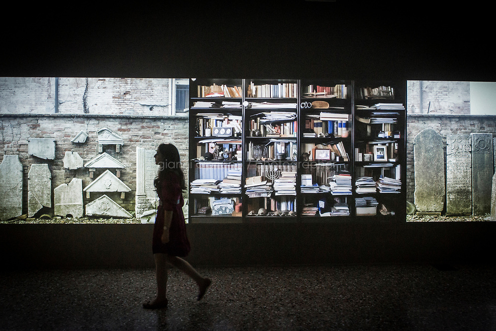 VENICE, ITALY - 11 MAY 2017: Artist Hadassa Goldvicht is seen here by her installation &quot;The House of Life&quot; at the Fondazione Querini Stampalia in Venice, Italy, on May 11th 2017.<br /> <br /> The House of Life, a poetic and expansive installation by<br /> Hadassa Goldvicht, explores themes of historical memory; the threshold between life, death,<br /> myth, and art; and the rapidly changing nature of Venice, via a multi-channel video work<br /> installed at the Querini Stampalia in conjunction with the Venice Biennale. Presented by the<br /> Israel Museum, Jerusalem, in collaboration with Meislin Projects, the exhibition follows<br /> Aldo Izzo, the 86-year-old guardian and keeper of the Jewish cemeteries in Venice.<br /> <br /> The 57th International Art Exhibition, titled VIVA ARTE VIVA and curated by Christine Macel, is organized by La Biennale di Venezia chaired by Paolo Baratta. &quot;Viva Arte Viva is an exclamation, a passionate outcry for art and the state of the artist. Viva Arte Viva is a Biennale designed with artists, by artists and for artists, about the forms they propose, the questions they ask, the practices they develop and the ways of life they choose&quot;, Christine Macel says. <br />  <br /> Rather than broaching a single theme, Viva Arte Viva offers a route that moulds the artists&rsquo; works and a context that favours access and understanding, generating connections, resonances and thoughts. VIVA ARTE VIVA will unfold over the course of nine chapters or families of artists, beginning with two introductory realms in the Central Pavilion, followed by another seven across the Arsenale through the Giardino delle Vergini. 120 are the invited artists from 51 countries; 103 of these are participating for the first time. <br /> <br /> The Exhibition will also include 85 National Participations in the historic Pavilions at the Giardini, at the Arsenale and in the historic city centre of Venice. 3 countries will be participating for the first