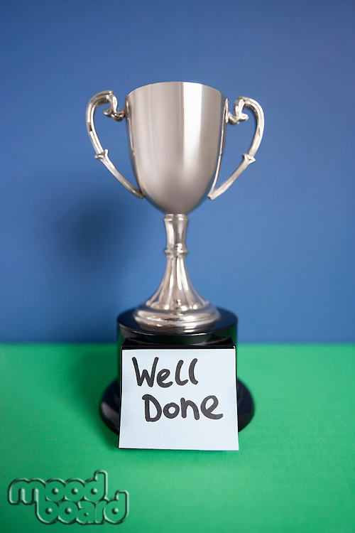 Winning trophy award with sticky note over colored background
