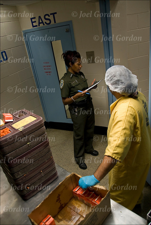 African American female Correction Officer on 3rd floor Main, with trusty inmate she is handing out meals and Conducting head count of every inmate in cells. Security check in General population unit / close unit.<br /> <br /> release #2320