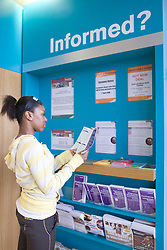 Young woman looking at information leaflets in the reception area at her sports leisure centre,