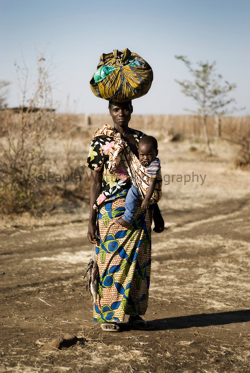 African mother carrying child in village