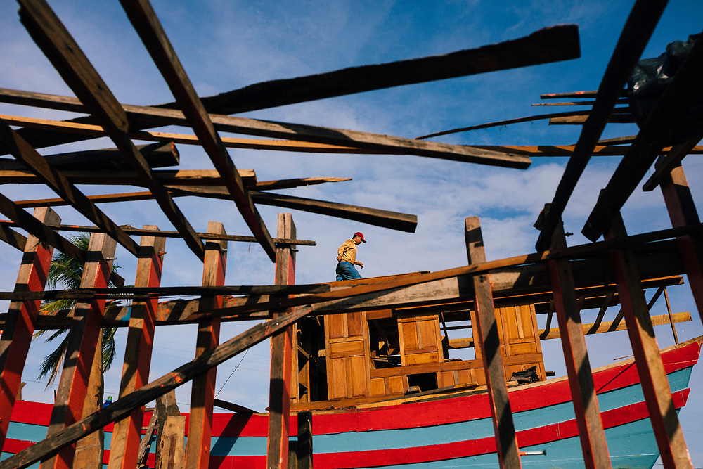 Men at work at a shipyard in central Vietnam, getting boats ready for the sea.