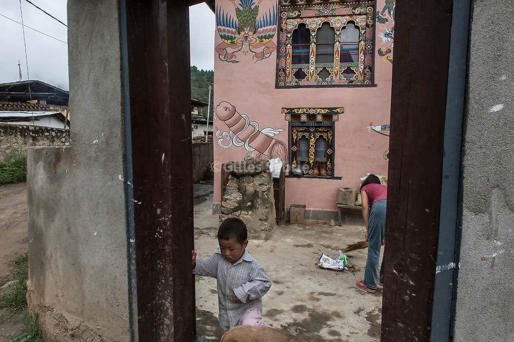 For a story by Steven Lee Myers, Bhutan<br /> Lobesa, Bhutan, August 2nd, 2017<br /> A family inside the courtyard of a traditional Bhutanese house decorated with elaborate paintings of mythical animals and that of a penis. Locals believe that the phallic symbols bring good luck and drives away evil spirits, Its origin can be found in the Bon religion that predated the advent of Tibetan Buddhism. Phallus representations are also linked to the XVIth century Lama Drukpa Kunley  popularly known as the &ldquo;Divine Madman&rdquo; for his unorthodox ways of teaching, and for his bizarre and shocking behaviours.<br /> Gilles Sabri&eacute; pour The New York Times
