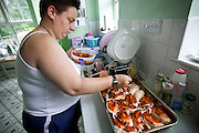 "Jill McTighe, a mother and school aide, bastes chicken for Sunday dinner in her kitchen in Willesden, London, United Kingdom. (Jill McTighe is featured in the book What I Eat: Around the World in 80 Diets.)  The caloric value of her day's worth of food on a ""bingeing"" day in the month of September was 12300 kcals. The calorie total is not a daily caloric average.  Jill is 31 years old; 5 feet, 5 inches tall;  and 230 pounds. Honest about her food addiction replacing a drug habit, Jill joked about being a chocoholic as she enthusiastically downed a piece of chocolate cake at the end of the photo session. Her weight has yo-yoed over the years and at the time of the picture she was near her heaviest; walking her children to school every day was the sole reason she didn't weigh more. She says this photo experience was a catalyst for beginning a healthier diet for herself and her family.  MODEL RELEASED. [Use of Jill McTighe images must be used contextually only and use cleared with Peter Menzel Photography on a case by case basis.]"