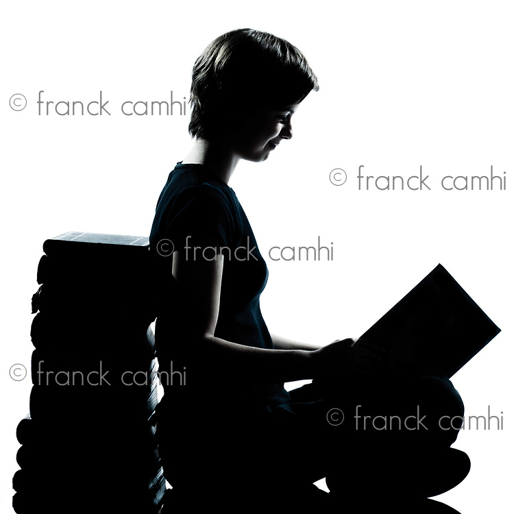 one caucasian young teenager silhouette boy or girl reading full length in studio cut out isolated on white background