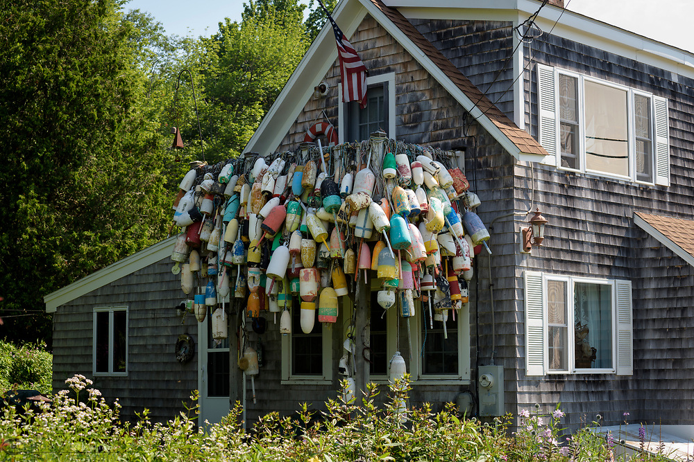 Old lobster bouys hang on a house in Spruce Head, Maine.