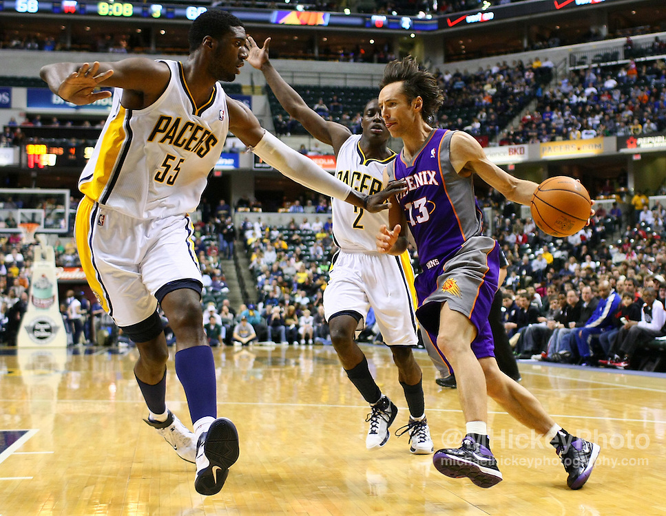 Feb. 27, 2011; Indianapolis, IN, USA; Phoenix Suns point guard Steve Nash (13) dribbles the baseline against Indiana Pacers center Roy Hibbert (55) and Indiana Pacers guard Darren Collison (2) at Conseco Fieldhouse. Phoenix defeated Indiana 110-108. Mandatory credit: Michael Hickey-US PRESSWIRE