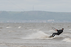 A lone kite surfer enjoys the wind and waves on a deserted Portobello Beach