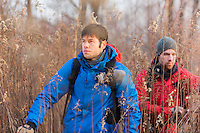 Young male hikers walking through field