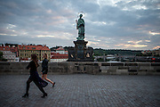 Early morning visitors are passing the St. John of Nepomuk Statue on Prague Charles Bridge during the change from night to day.