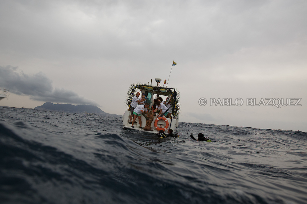 15/08/2016. Fishermen and divers lift an sculpture of the Virgin of Palm on to a boat from the water during the yearly Virgin of Palm maritime pilgrimage on August 15, 2016 in Algeciras, Spain. The Our Lady of Palm maritime pilgrimage in Algeciras dates back to 1975 and takes place annually when fishermen rescue the submerged virgin from the deep sea. Worshippers amid thousands of visitors await its arrival at the Rinconcillo beach. The devotion for the Virgin of Palm comes from the seventeenth century when a ship coming from Italy docked at Algeciras port to wait out bad weather. According to legend, once the crew of the ship removed a box with an image of the Virgin from its cargo the weather turned and the sea's tides were calmed. (© Pablo Blazquez)