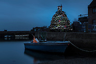 A Christmas tree constructed entirely from lobster pots glitters on the quayside in Emsworth, Hampshire where local fishermen have developed a unique way to raise funds and awareness for their industry. <br /> Each pot has been bought by a local person, family or local business for &pound;35 and they will each receive the first crustacean caught in the traps next year.<br /> Emsworth has just two remaining fishermen, Kelvin Cole and Peter Williams.<br /> February 2014 saw some horrific storms causing some terrible damage. Kelvin&rsquo;s boat sank on its mooring and Peter lost all his whelk, cuttle and lobster pots which he has been unable to replace.<br /> This Saturday (19th December) crowds will gather round the tree to enjoy carol singing and lobster bisque in aid of the RNLI.<br /> Emsworth was once a thriving fishing village with 3,000 people working in the oyster trade. At the height of successful industry, over three million oysters a year came out of Emsworth to be distributed across the country. But the centuries old industry disappeared almost overnight in 1902 when the Dean of Winchester died from typhoid attributed to infected oysters. When the beds were inspected, it became apparent that they were contaminated from sewage. <br /> Picture date: Wednesday December 16, 2015.<br /> Photograph by Christopher Ison &copy;<br /> 07544044177<br /> chris@christopherison.com<br /> www.christopherison.com