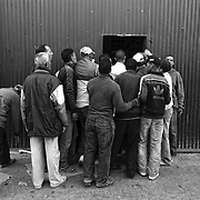 CEUTA, SPAIN - JUNE 27, 2010 : Moroccan porters crowded at the door of one the warehouses next to the cross border of El Biutz, looking for transport goods to Morocco. Thousands  of people are involved in transporting smuggled goods from Ceuta (an Spanish enclave on the North African coast) to Morocco, it is estimated that every day enter 10.000 porters, mostly women, that it make between three and five trips to Morocco with all types of products purchased on  the warehouse border area of El Biutz in Ceuta, Spain.( Photo by Jordi Cami )