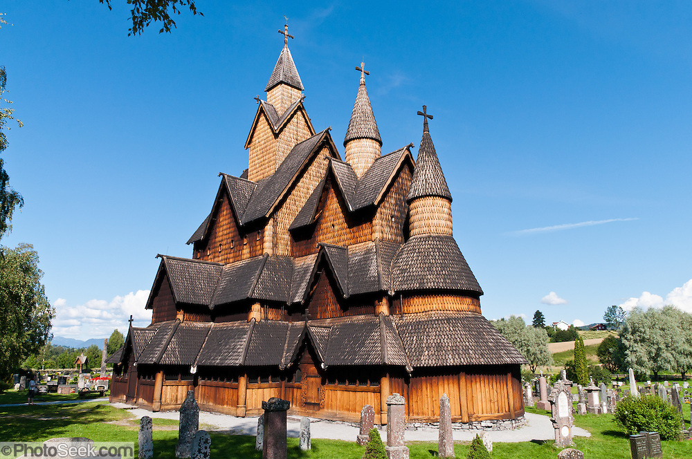 """Heddal stave church, Norway's largest stave church, rises above cemetery headstones and survives beyond many generations. This triple nave stave church, which some call """"a Gothic cathedral in wood,"""" was built in the early 13th century and restored in 1849-1851 and the 1950s. Heddal stavkirke is in Notodden municipality, Telemark County, Norway. Panorama stitched from 6 overlapping photos."""