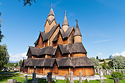"Heddal stave church, Norway's largest stave church, rises above cemetery headstones and survives beyond many generations. This triple nave stave church, which some call ""a Gothic cathedral in wood,"" was built in the early 13th century and restored in 1849-1851 and the 1950s. Heddal stavkirke is in Notodden municipality, Telemark County, Norway. Panorama stitched from 6 overlapping photos."