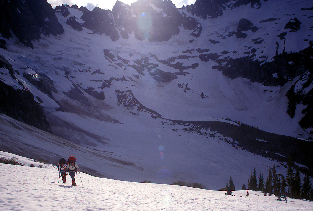 Forrest Murphy and Marshall Balick hike up to Luna Pass from Lousy Lake with the North Pickets surrounding them.