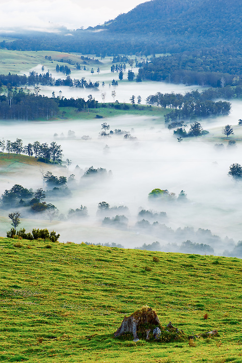 A valley hides in secret below the morning fog, Australia.