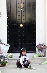 A young  girl  lays a flower outside Baroness Thatcher's house in London, Wednesday, 10th April 2013 Photo by: Stephen Lock / i-Images