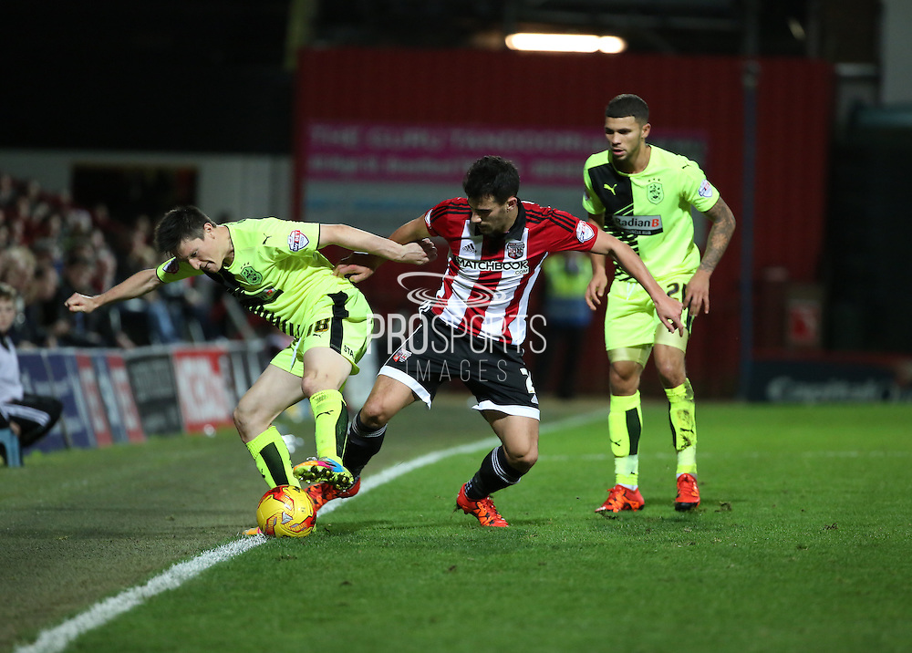 Brentford defender Maxim Colin battling for the ball with Huddersfield Town striker Joe Lolley during the Sky Bet Championship match between Brentford and Huddersfield Town at Griffin Park, London, England on 19 December 2015. Photo by Matthew Redman.
