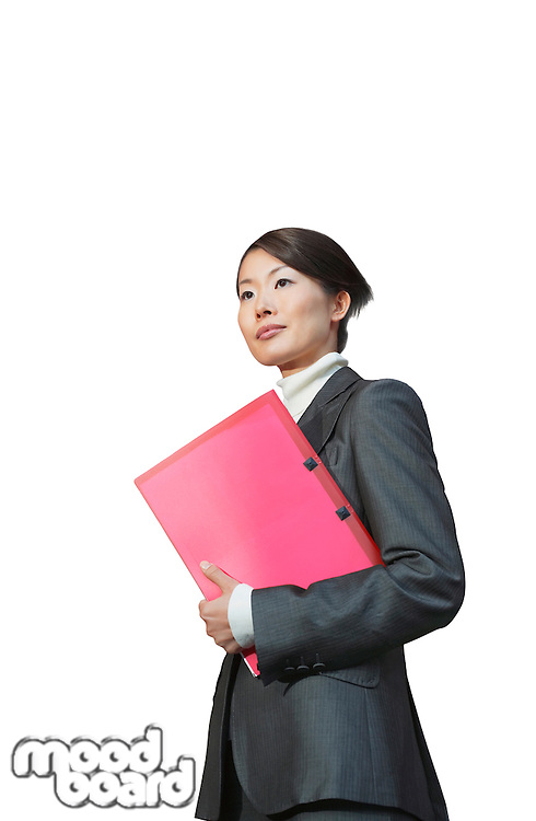 Young businesswoman with pink file standing against white background