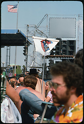 The crowd, deadheads, hanging out before concert begins at Roosevelt Stadium 4 August 1976. Pole with a flag draping wood crossbar. Microphones or cables unseen, hopefully added later when it was cooler out. Or a missed opportunity from that sonically awesome spot.